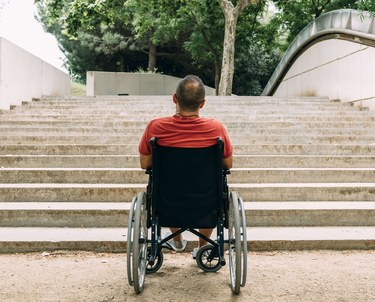 Man in wheelchair stopped at bottom of stairs with no ramp access