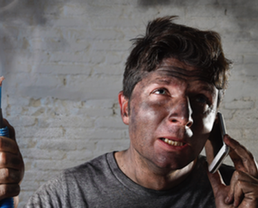 Electrician on phone holding burnt wires