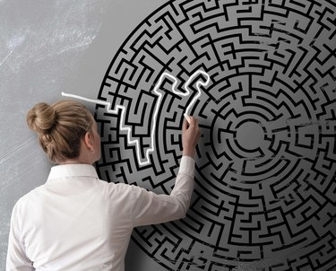 Woman trying to find way through chalk drawing of maze on blackboard challenge concept