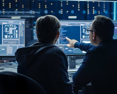 Two IT Professionals discussing desktop computer display