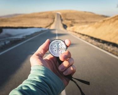 Person Holding Compass With Long Road into Desert
